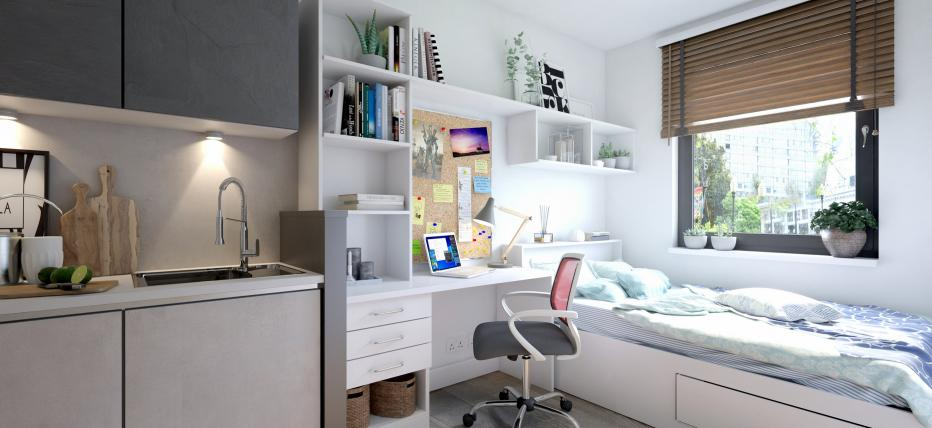 Bed, desk area with chair. Kitchen area with sink and cupboards