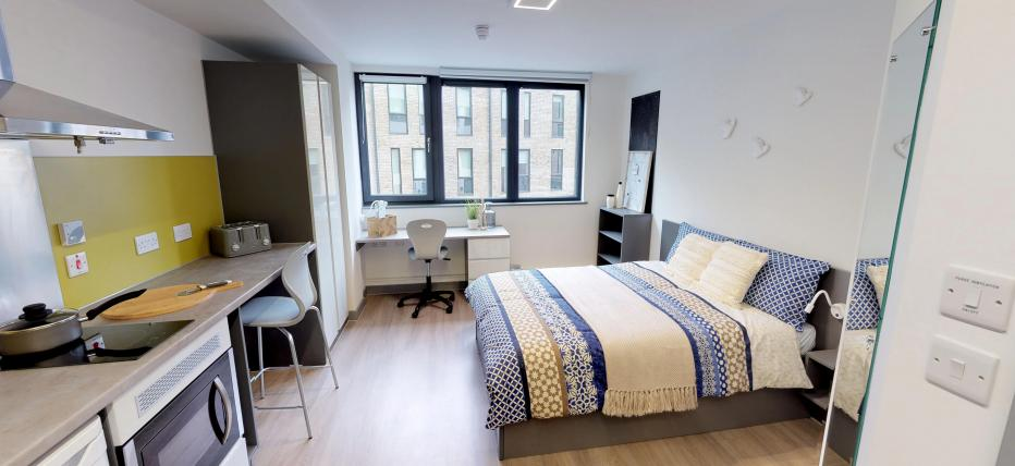 Bed, desk area and kitchen area with breakfast bar