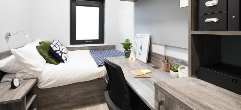 Bedroom with bed, desk and shelves