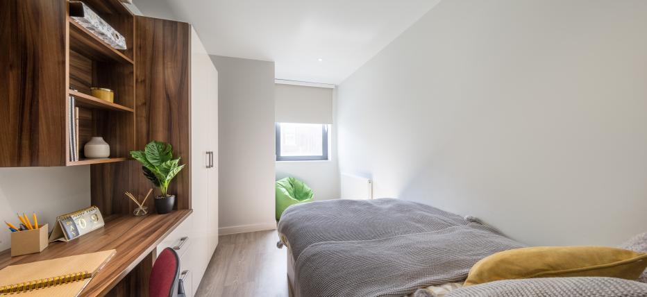 Bed, desk area and wardrobe