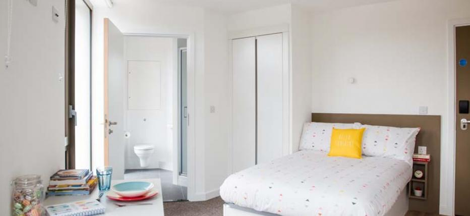 Bed, wardrobe, dining table and view to en-suite bathroom
