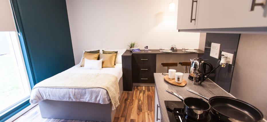 Bed, kitchen area with work surface, hob and oven, breakfast bar with stools