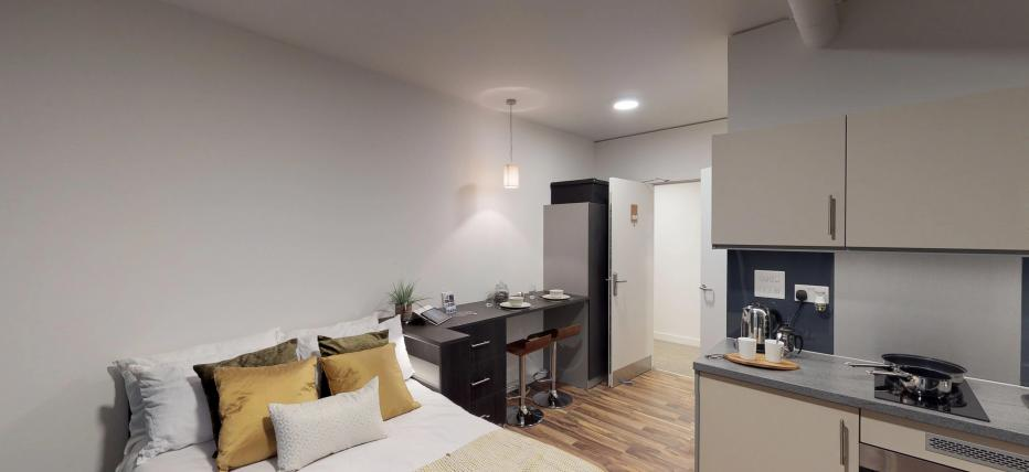 Bed, kitchen area with oven and hob. Breakfast bar with stools
