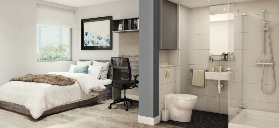 Bedroom with bed, desk and bathroom. Open bathroom area with walk-in shower, sink, mirror and toilet