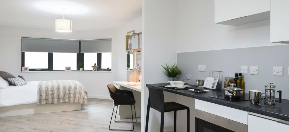 Bed with desk area and chair.Kitchen with breakfast bar and stool