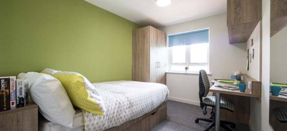 Bedroom with bed, desk and mirror
