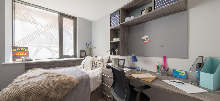 Bedroom with bed, desk and noticeboard