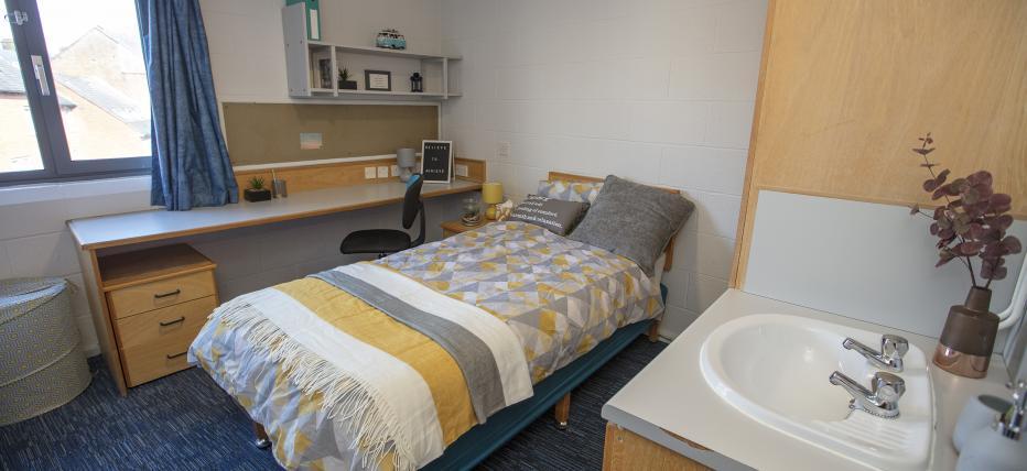 Bedroom, single bed, sink, window, desk, chair, shelves, noticeboard