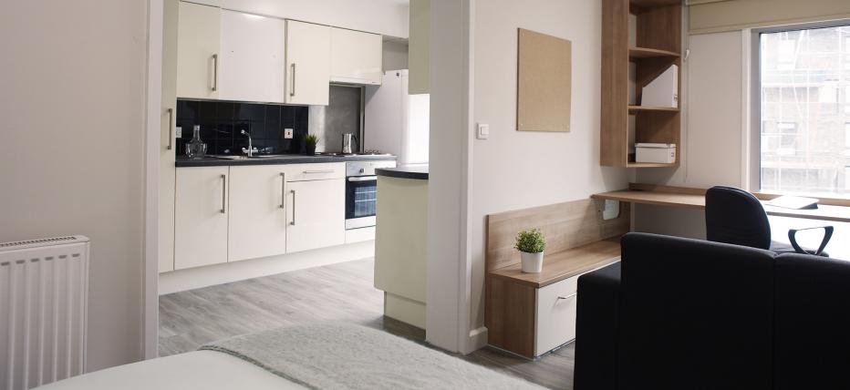 Bed, desk and chair. Archway to kitchen area