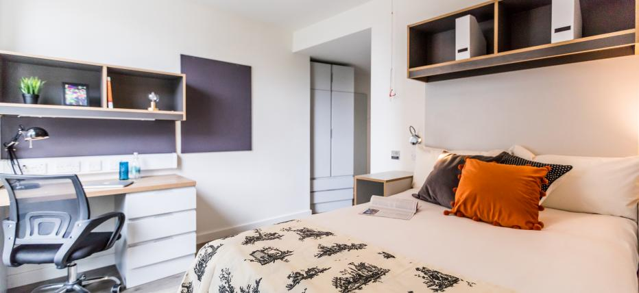 Bedroom with bed, bedside table, shelving and desk with chair