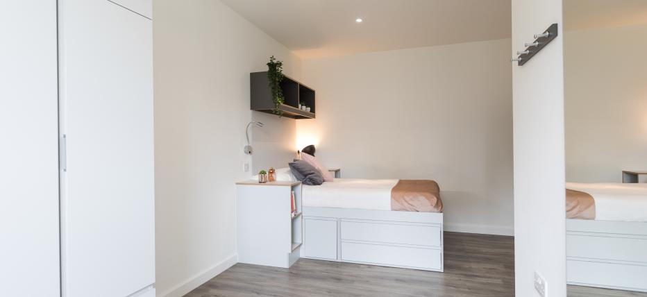 Bedroom with bed, bedside table, desk with chair