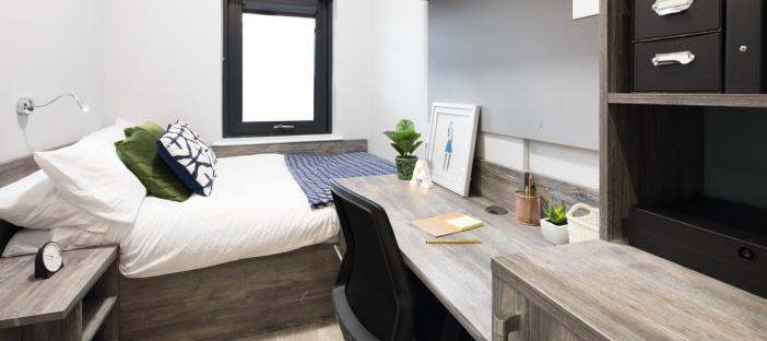 Bedroom with bed, desk and shelving