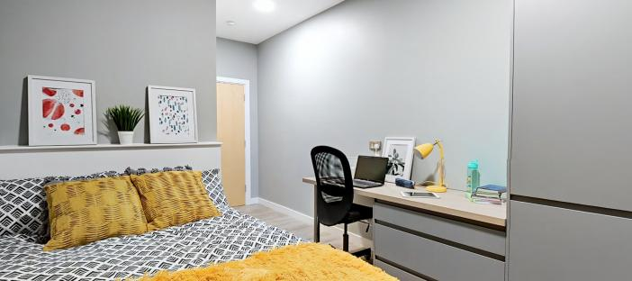 Bed with desk area and wardrobe