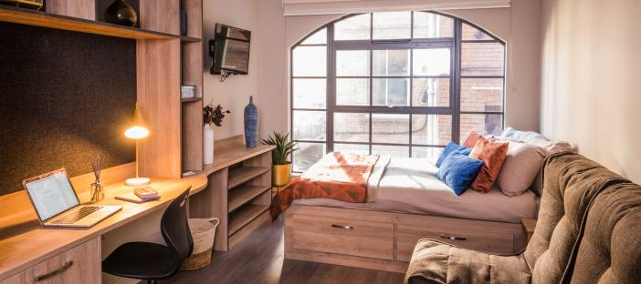 Large window, bed, comfy chairs, tv on wall and a desk.