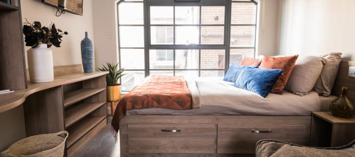 Bed, large window, wall-mounted tv and shelves