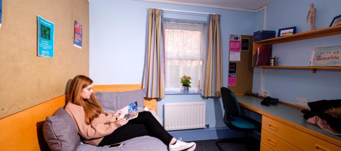 Bedroom, bed, desk, chair, radiator, shelves, noticeboard