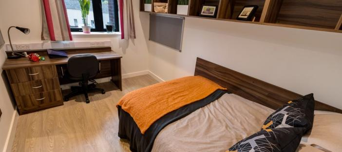 Bed, desk area and chair with shelving on the wall
