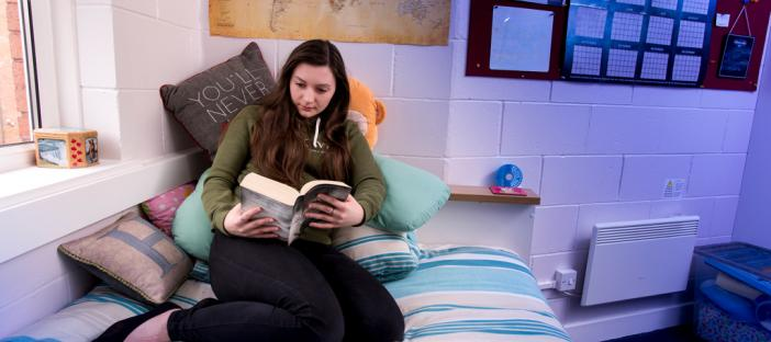 Room, bed, window by the bed, student sitting on the bed reading a book, large noticeboard on the wall, shelf next to the bed, radiator under the noticeboard