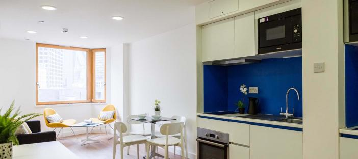 Kitchen Area with oven, cupboards and work surface. Dining table and chairs