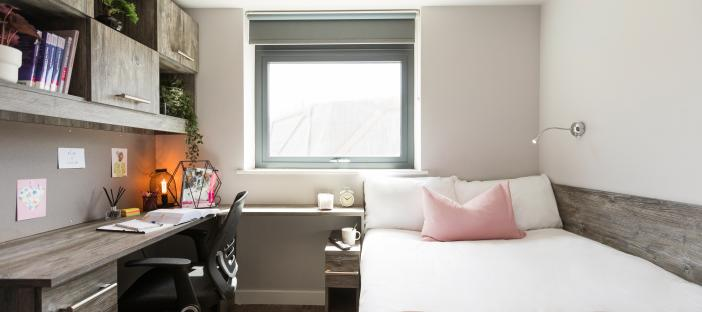 Bed, desk area with chair and shelving above