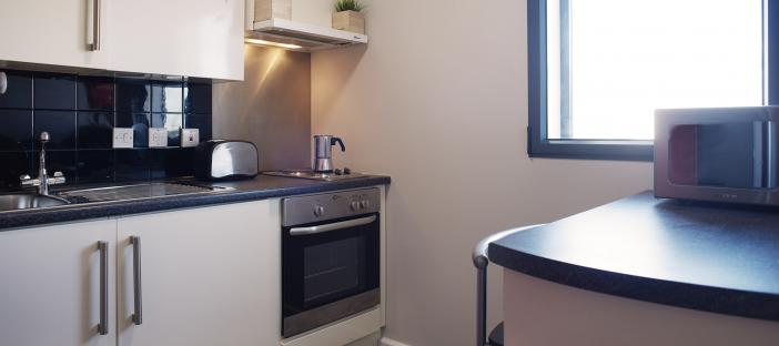Kitchen area with cupboards, work surface, oven and breakfast bar